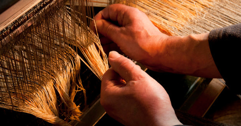 The Harris Tweed® weaver ties in the yarns by hand.